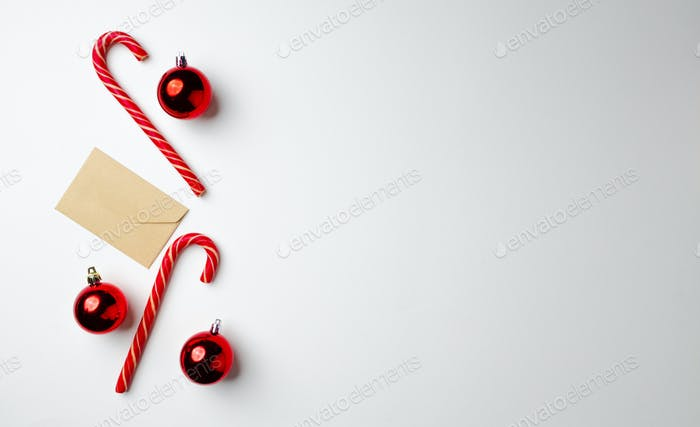 Candy canes and Christmas baubles on white background