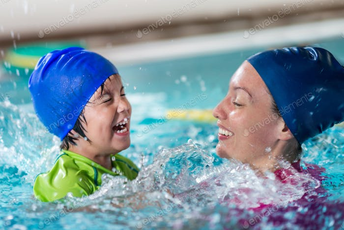 Swimming class fun, little boy with instructor