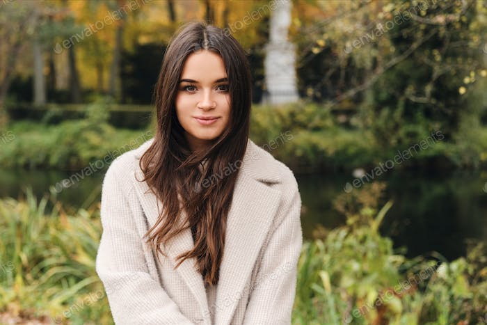 Attractive brunette girl in coat dreamily looking in camera in beautiful city park