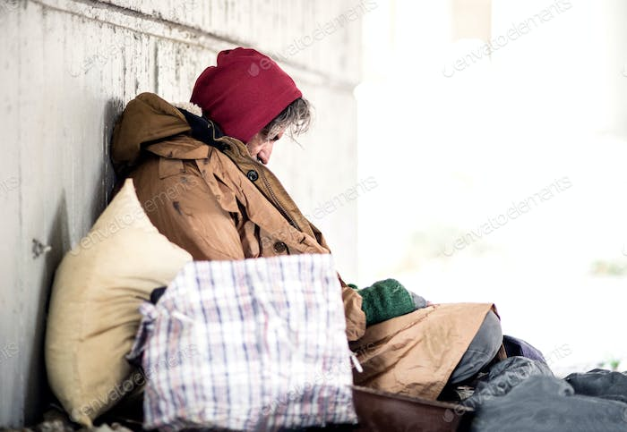 A side view of homeless beggar man sitting outdoors, leaning against a wall. Copy space.