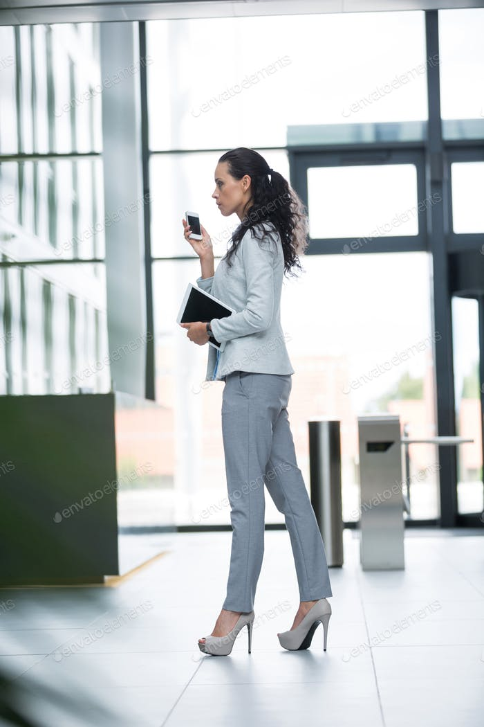 Businesswoman holding digital tablet and mobile phone