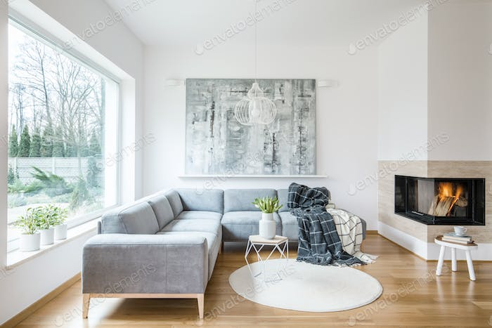 White sitting room interior with grey corner sofa, tulips in vas