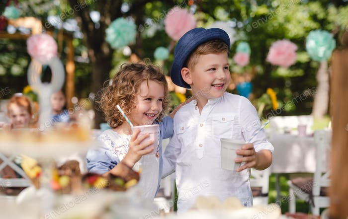 Small children standing outdoors in garden in summer, holding drinks.