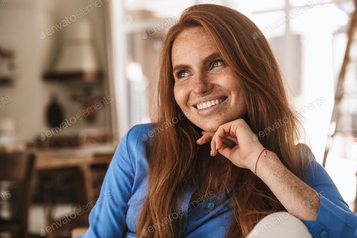 Image of happy ginger woman smiling and looking aside
