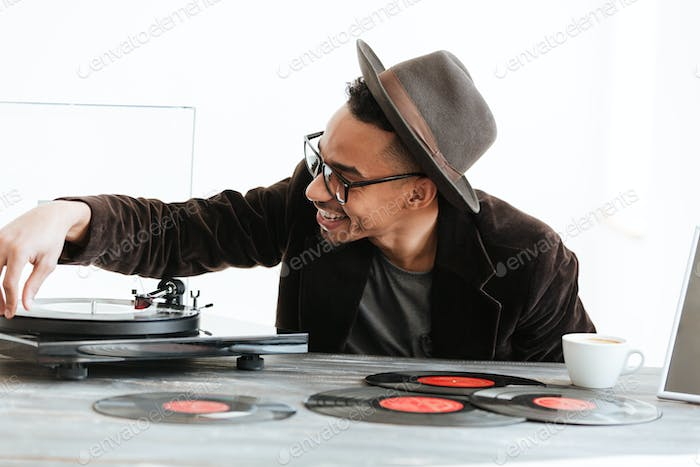 Happy African man using record-player