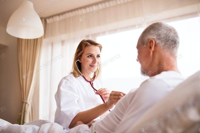 Health visitor and a senior man during home visit. Foto von ...