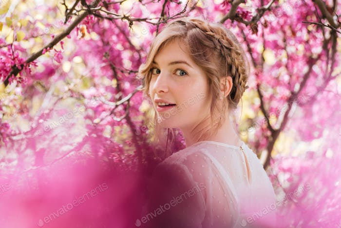 Happy woman walking in blooming garden