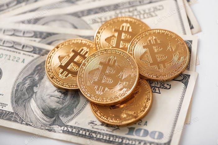 Pila de bitcoins de oro como la criptomoneda más popular en todo el mundo que se encuentra en billetes de dólar