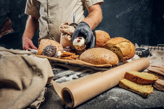 Bearded baker wearing a uniform standing next to a table with delicious bread loaves, baguettes