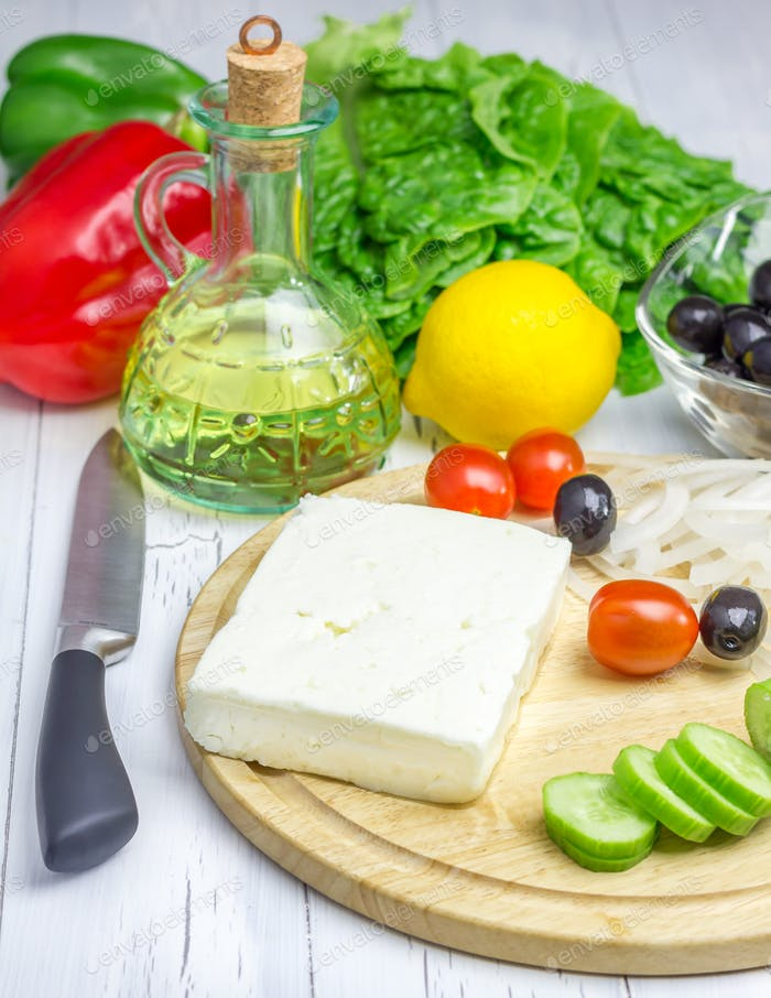 Ingredients for greek salad on the cutting board and wooden table