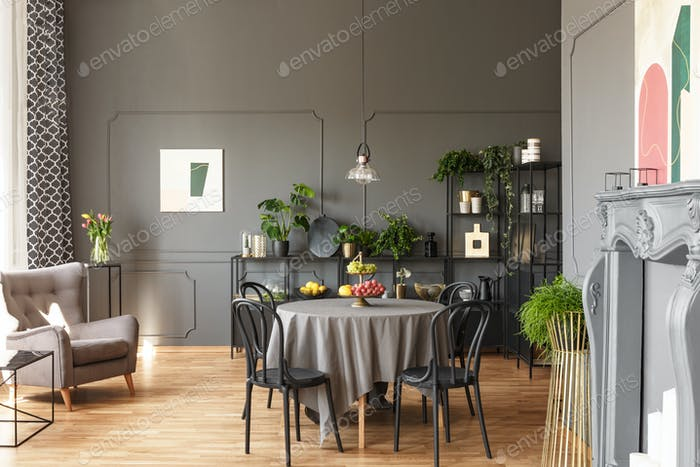 Black chairs at round table under lamp in grey loft interior wit