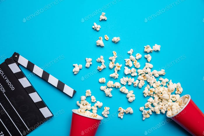 Clapperboard and pop corn on blue color background, top view