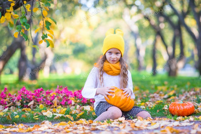 Adorable little girl with pumpkin outdoors at beautiful autumn day. Trick or treat