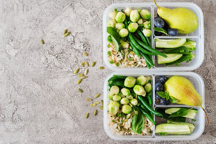 Vegan green meal prep containers with  rice, green beans,  brussel sprouts, cucumber and fruits.