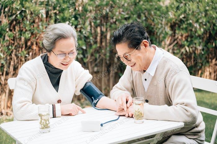 Seniorenpaar überprüfen ihren Blutdruck auf dem Hof
