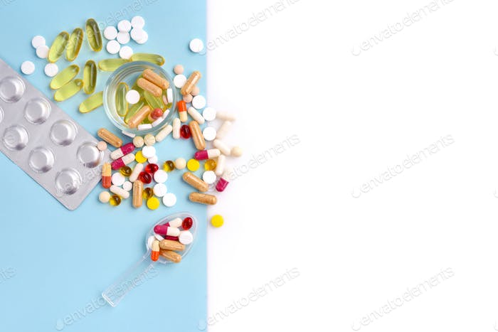 Assorted pharmaceutical medicine pills, tablets and capsules on blue and white background