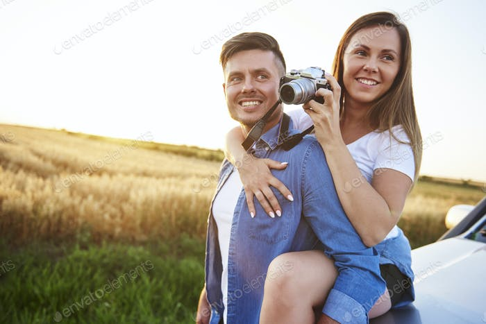 Loving couple with camera in outdoor.