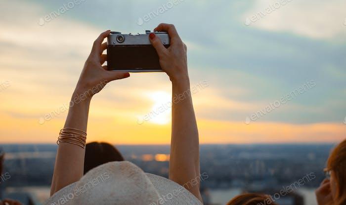 joven chica tomando puesta de sol foto en el techo