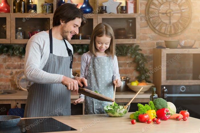 Familie Kochen. Fröhliche Papa und kleine Tochter Vorbereitung Gesundes Mittagessen zusammen
