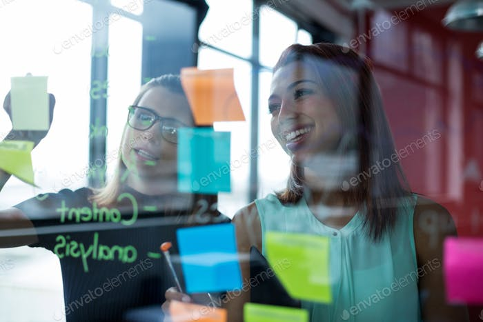 Business executives writing over sticky notes on glass