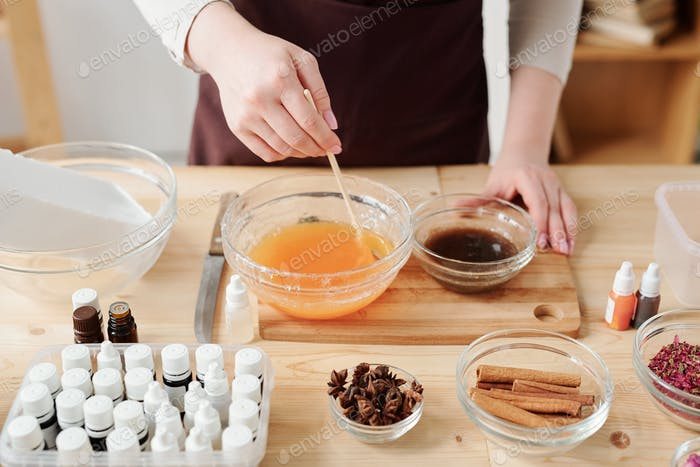 Craftswoman mixing liquid soap mass with orange essential oil in bowl
