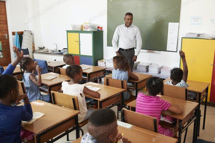 Lehrer und Kinder während eines Unterrichts an einer Grundschule