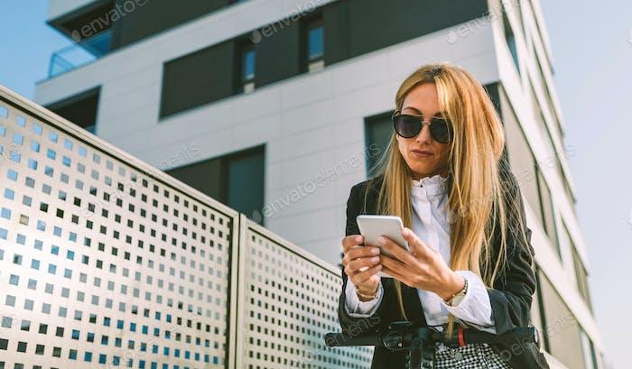 Geschäftsfrau mit Elektroroller Blick auf das Handy