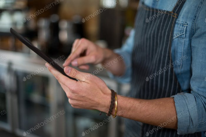 Mid section of waiter using digital tablet
