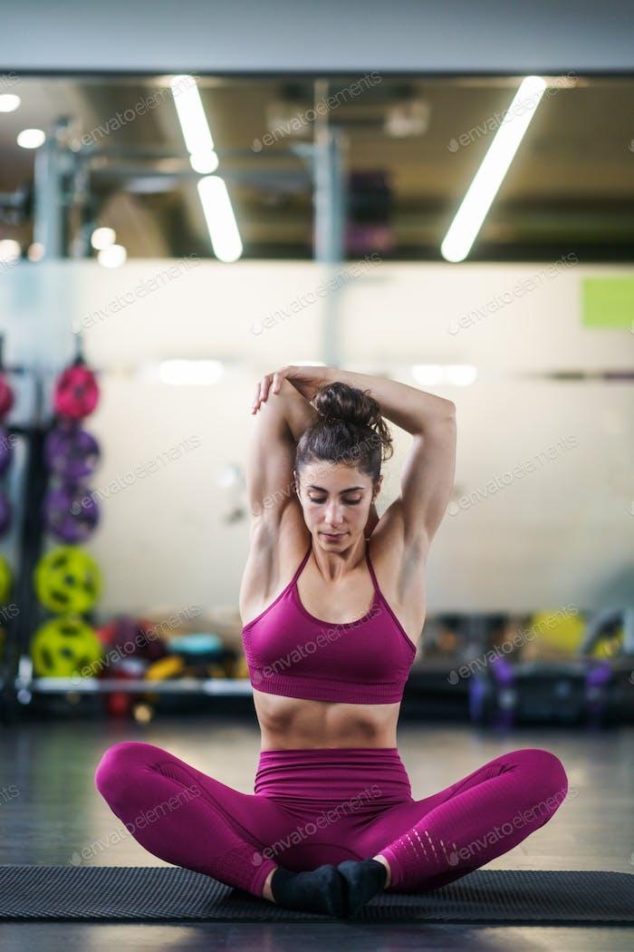 Mujer joven haciendo ejercicios de estiramiento en una estera de yoga