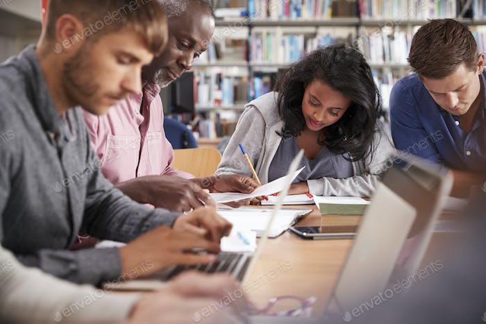 Group Of Mature College Students Working On Project In Library