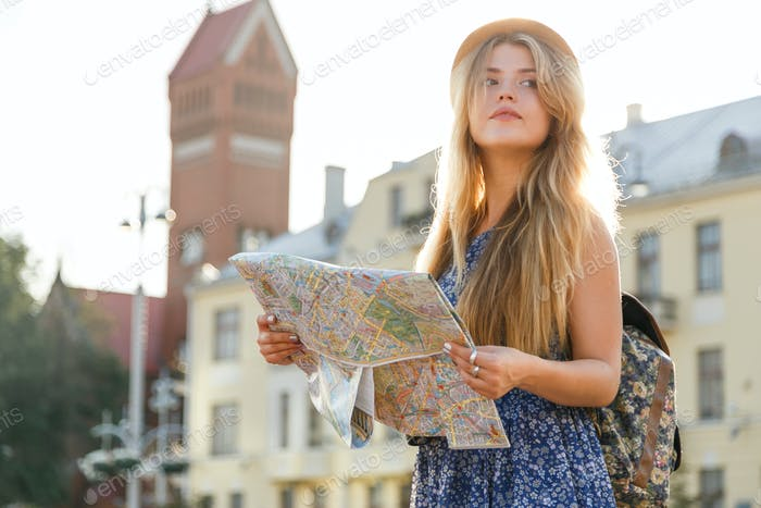 stylish traveler hipster woman portrait with camera and hat holding map on the street