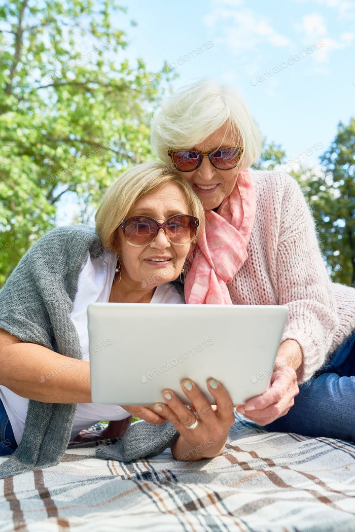 Senior Women Using Laptop in Park