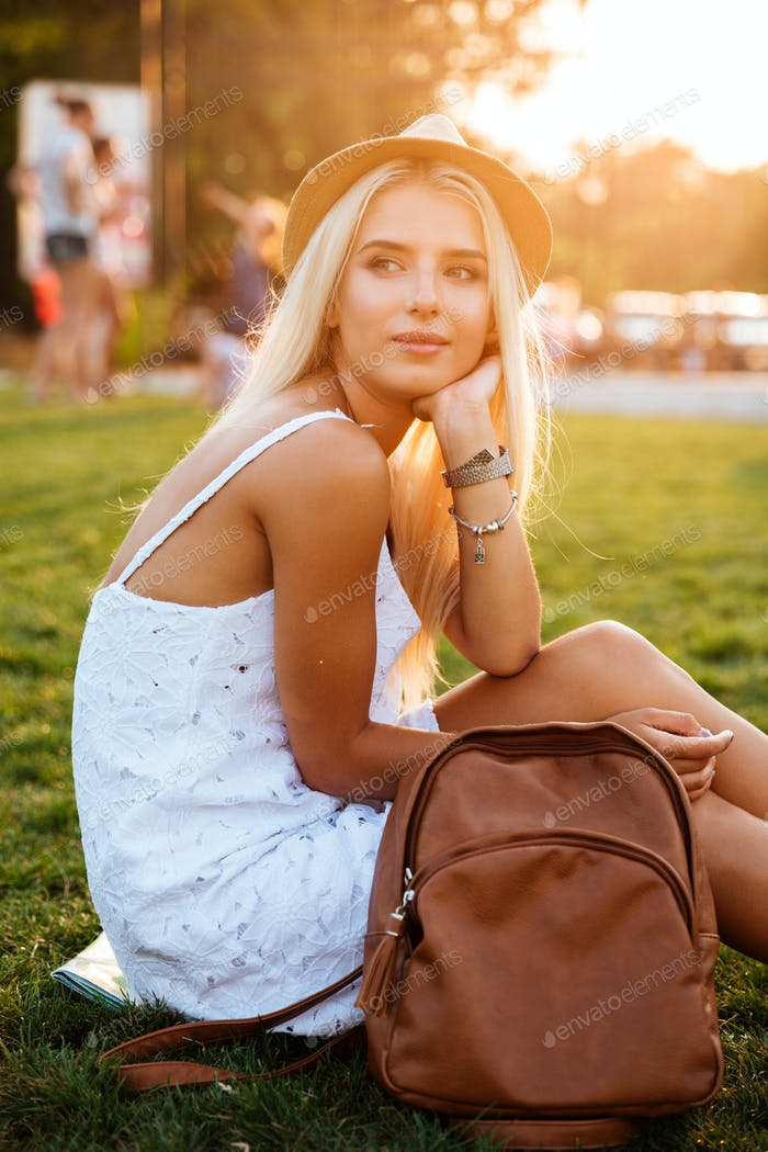 Beautiful blonde young woman with backpack sitting in the park