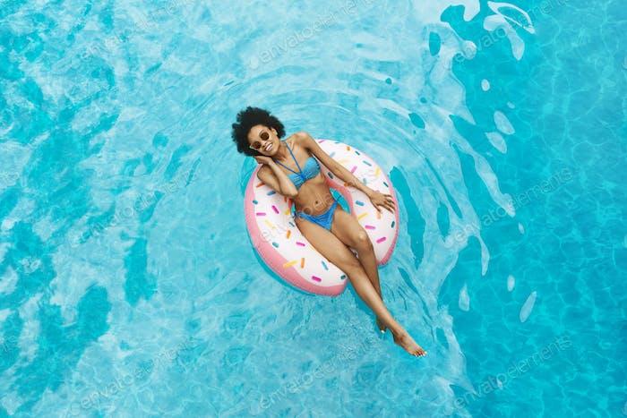 Millennial Afroamerikanisches Mädchen in sexy Bademode schwimmt auf Donut Ring am Pool