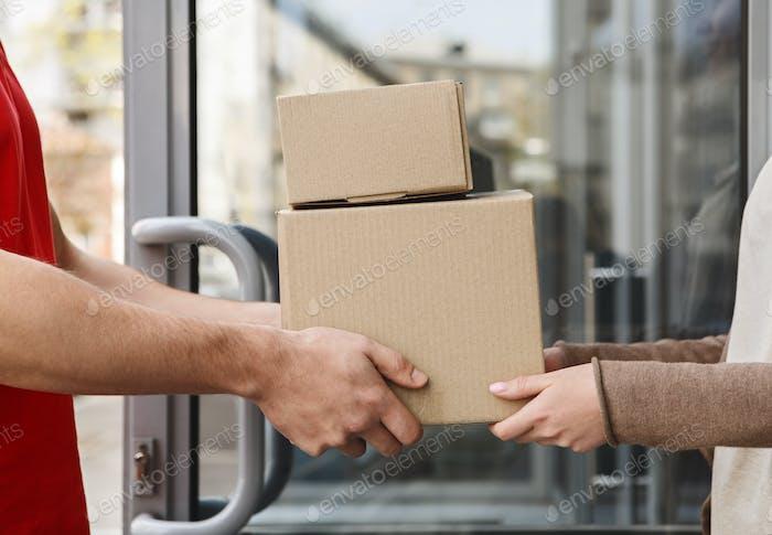 Garantiert exzellenten Service. Hände von Kunden und Kurier halten Pakete