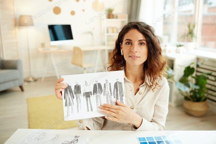 Clothes Designer Demonstrating Sketches
