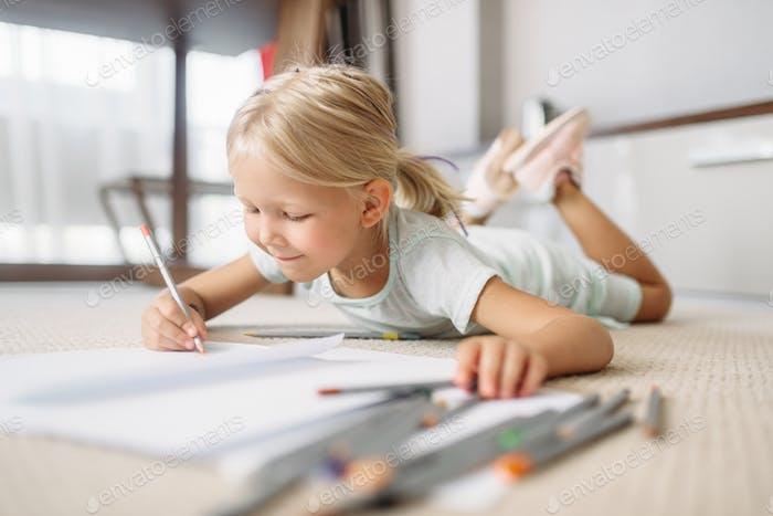 Little girl draw lying on the floor at home