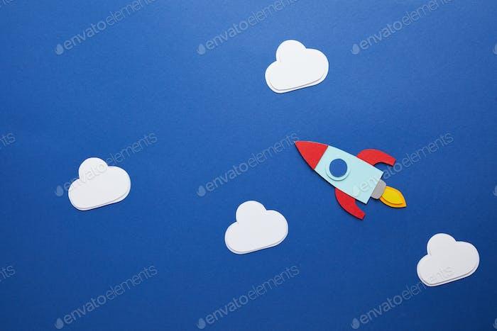 nubes blancas y cohete sobre fondo azul