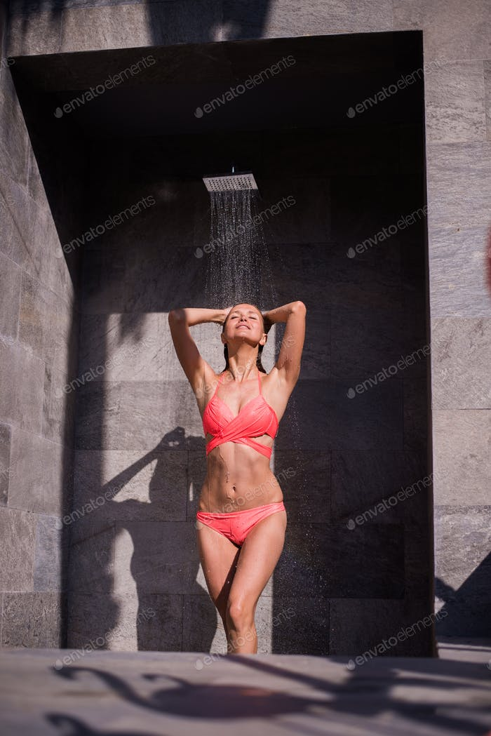 Attractive sexy woman under the shower outdoors near swimming pool at luxury hotel resort