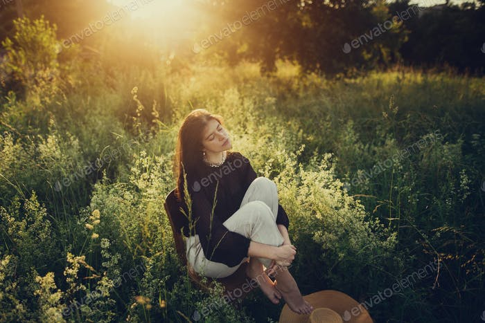 Fashionable woman relaxing in summer countryside