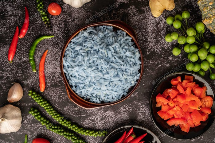 Butterfly Pea flower rice in a brown cup with spices on black cement.