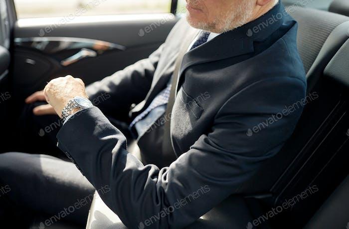 senior businessman driving on car back seat