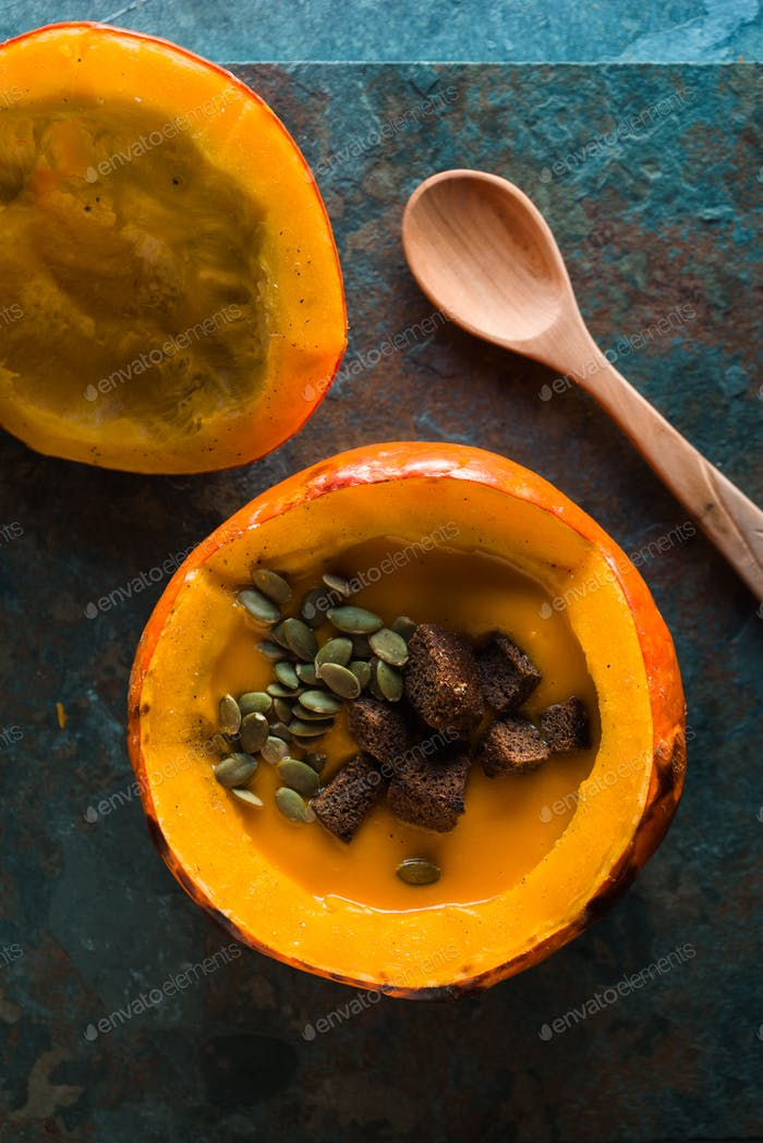 Pumpkin soup with seeds and croutons in a pumpkin and a spoon