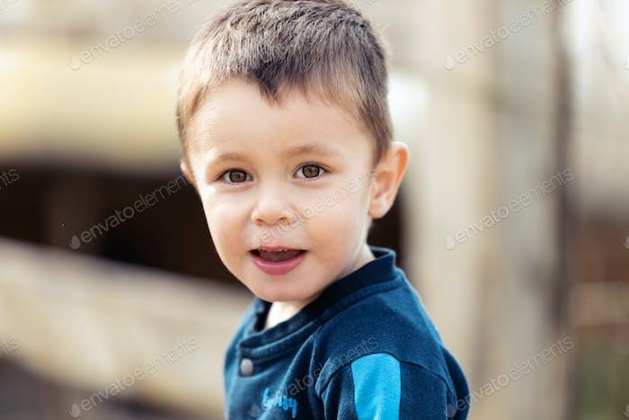 Netter kleiner Junge, der sich die Kamera im Freien ansieht.