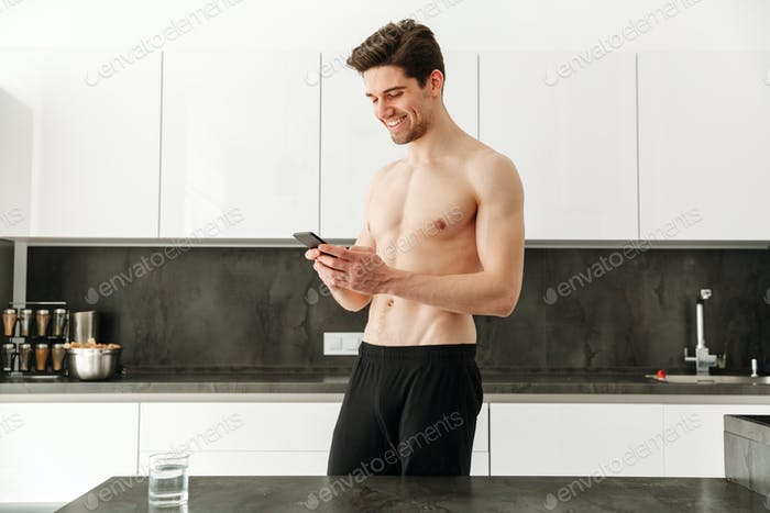 Happy cheerful naked man standing in kitchen