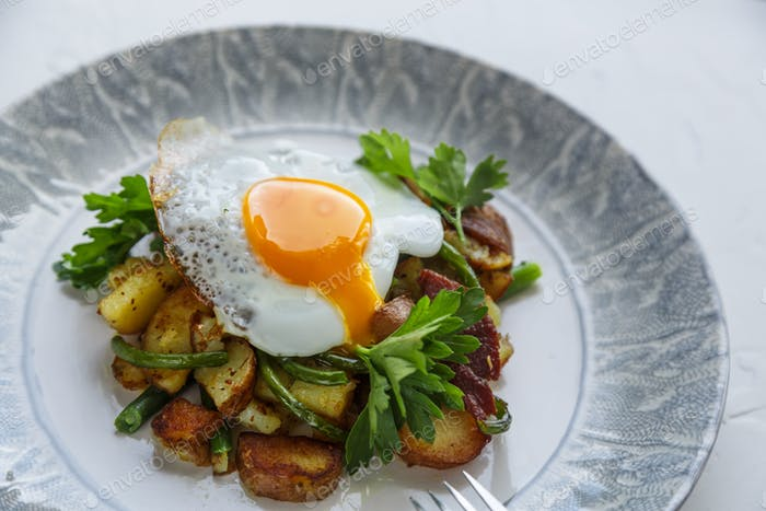 Runing yolk on fried potato and garlic sprouts