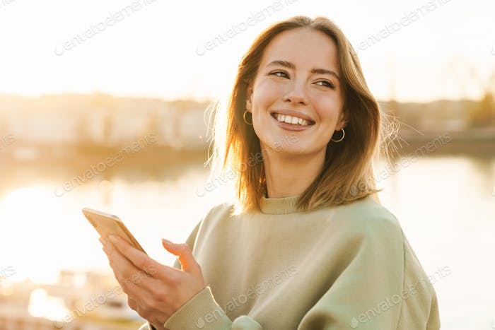 Portrait of cheerful woman using cellphone while walking on promenade