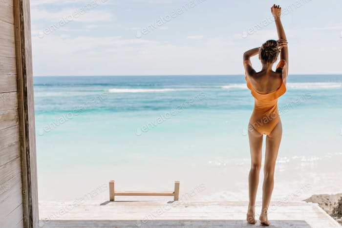 Barefooted girl in orange swimsuit looking at ocean in morning. Outdoor photo of relaxed female mod