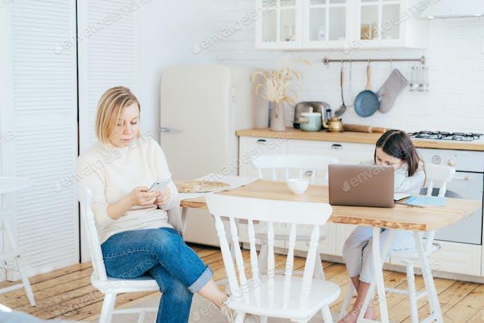 Mamá se comunica en una red social en el teléfono, hija hace los deberes en la mesa con una computadora portátil