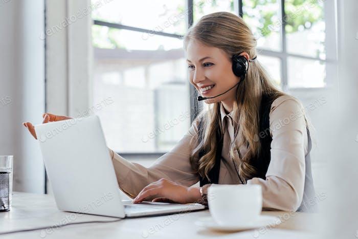selektiver Fokus des fröhlichen Bedieners im Headset lächelnd in der Nähe von Laptop und Tasse